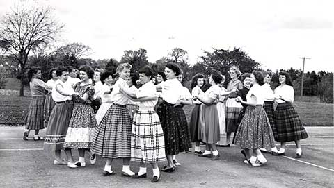 This is a 1955 photo of students from Miss Shogren's square dancing class dancing on the tennis courts.