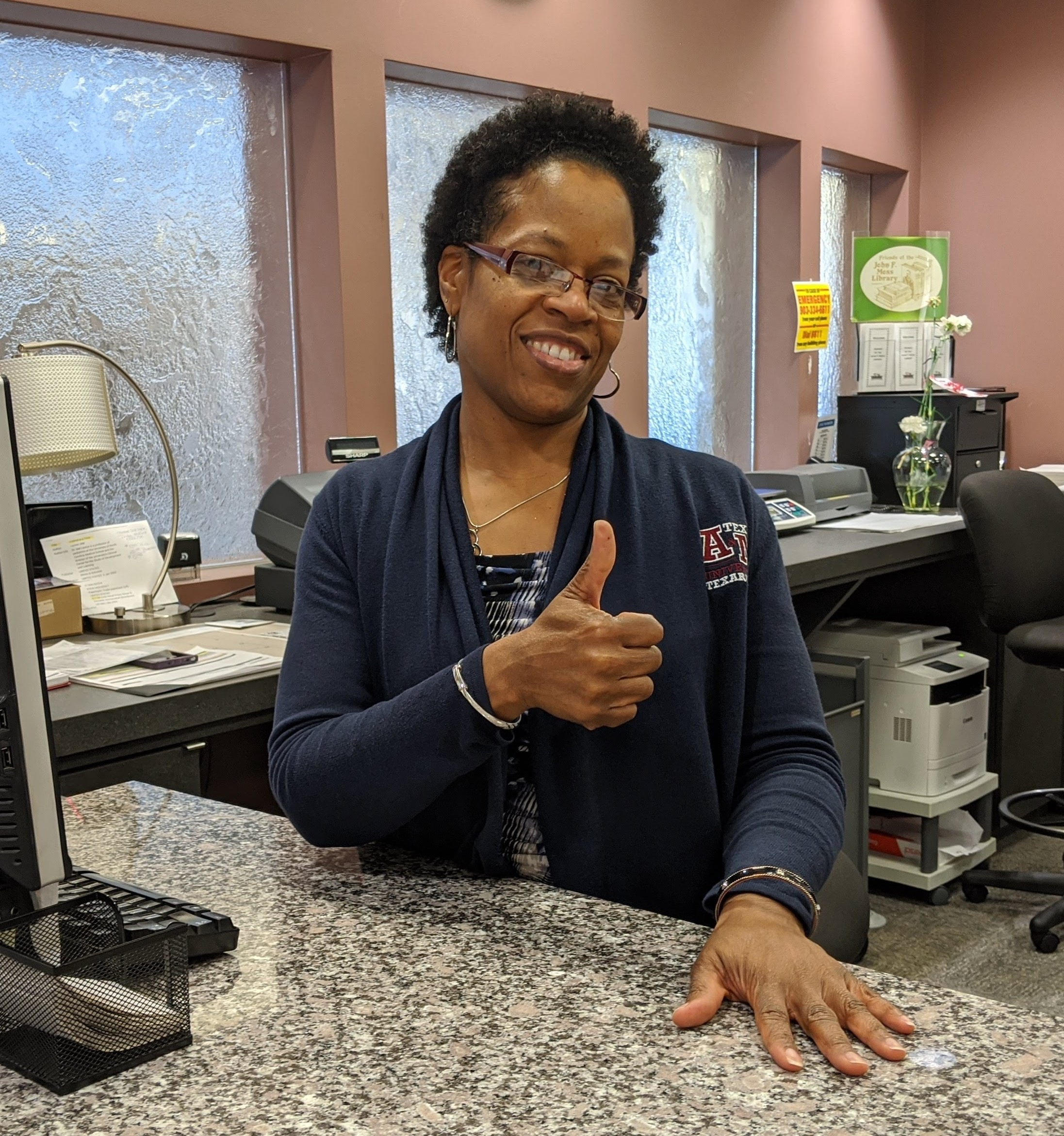 woman at front desk giving a thumbs up