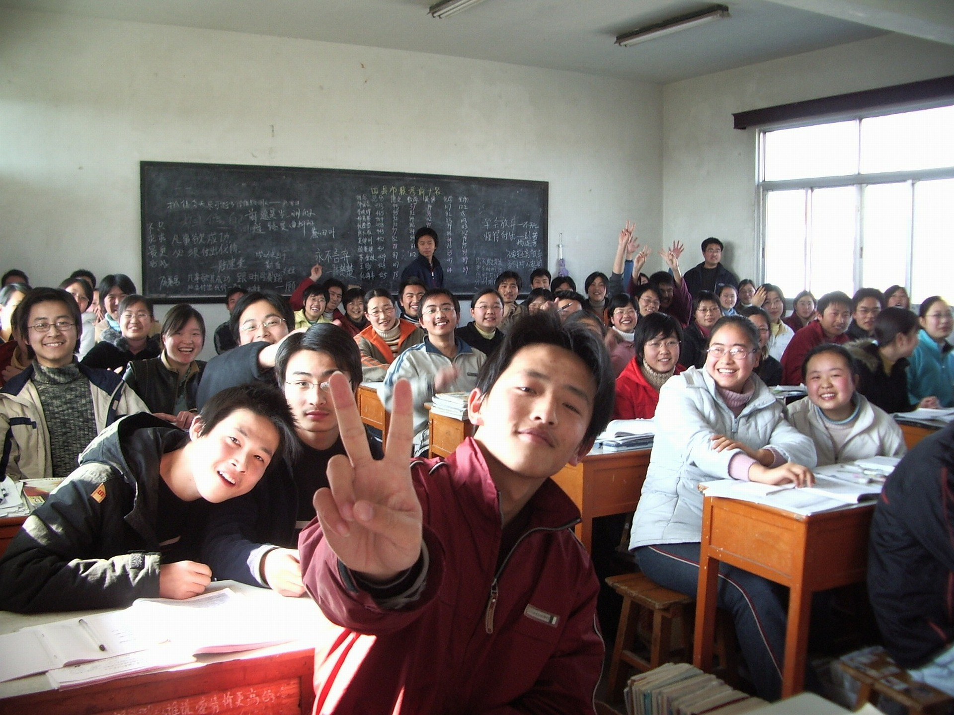 Class of students at desks smiling for the camera