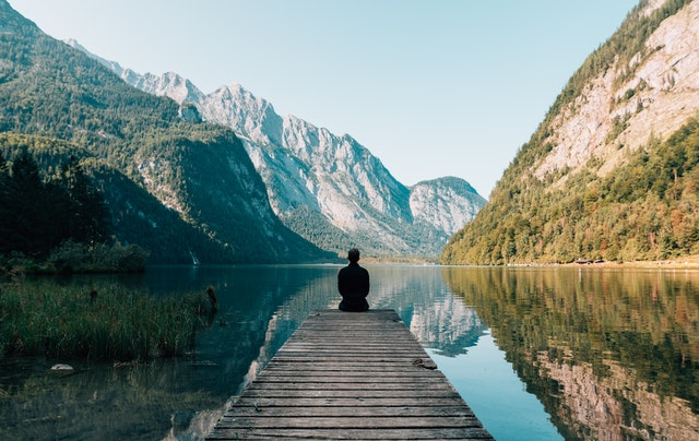 Person sitting on bridge in front of lake and mountain landscape