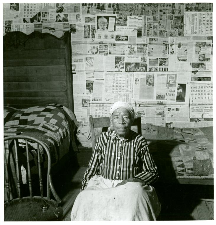 Picture of Ex-slave, Greensboro, Alabama sitting in a bedroom near two quilt-covered beds.