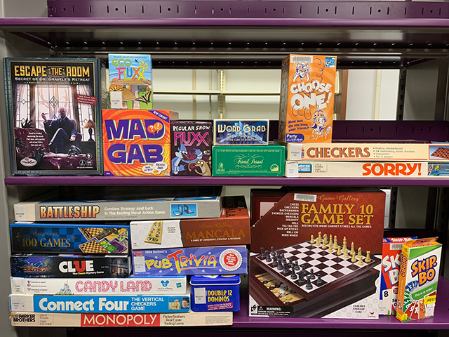 A variety of board games stacked on the shelf.