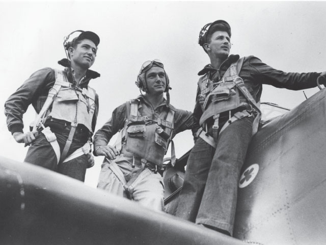 black and white historical photo of three men standing on the wing of a military airplane