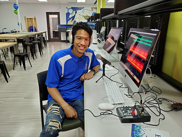 Student sitting at computer station in the I-Create Lab with headphones using podcasting equipment and software