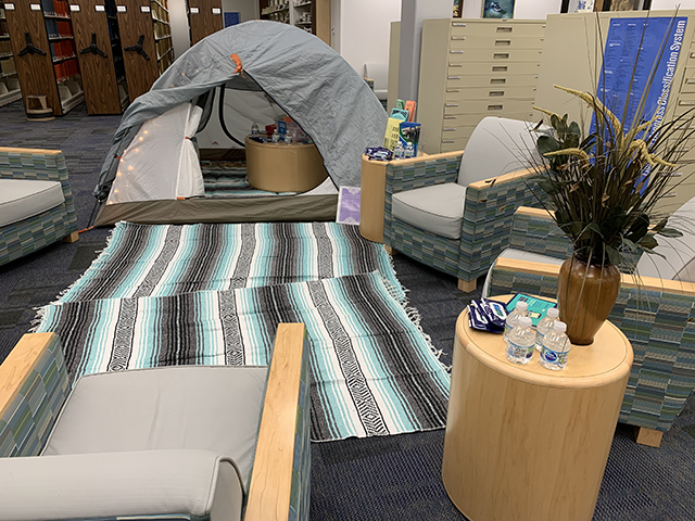 Tent set up in library with blankets, pillows, and tips and tools for relaxing