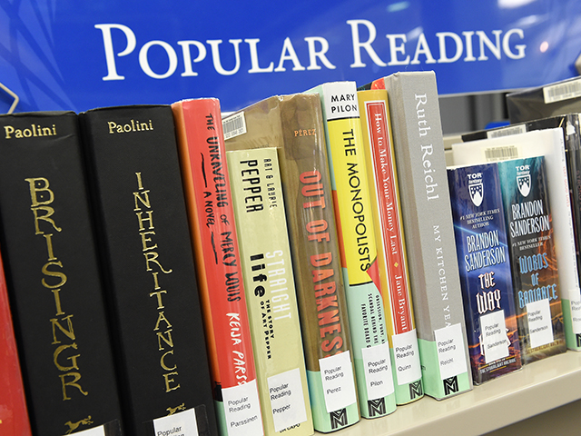 blue sign that reads, popular reading with a shelf of books below.