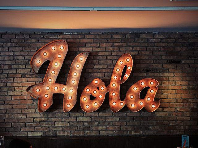 "image of metal ""Hola"" lighted sign hanging on brick wall"
