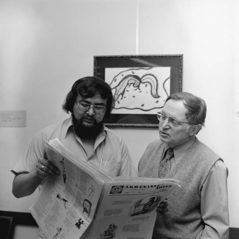 "Two men reading ""Akwesasne Notes"" newspaper in the Indian Studies Room, UMD Library"