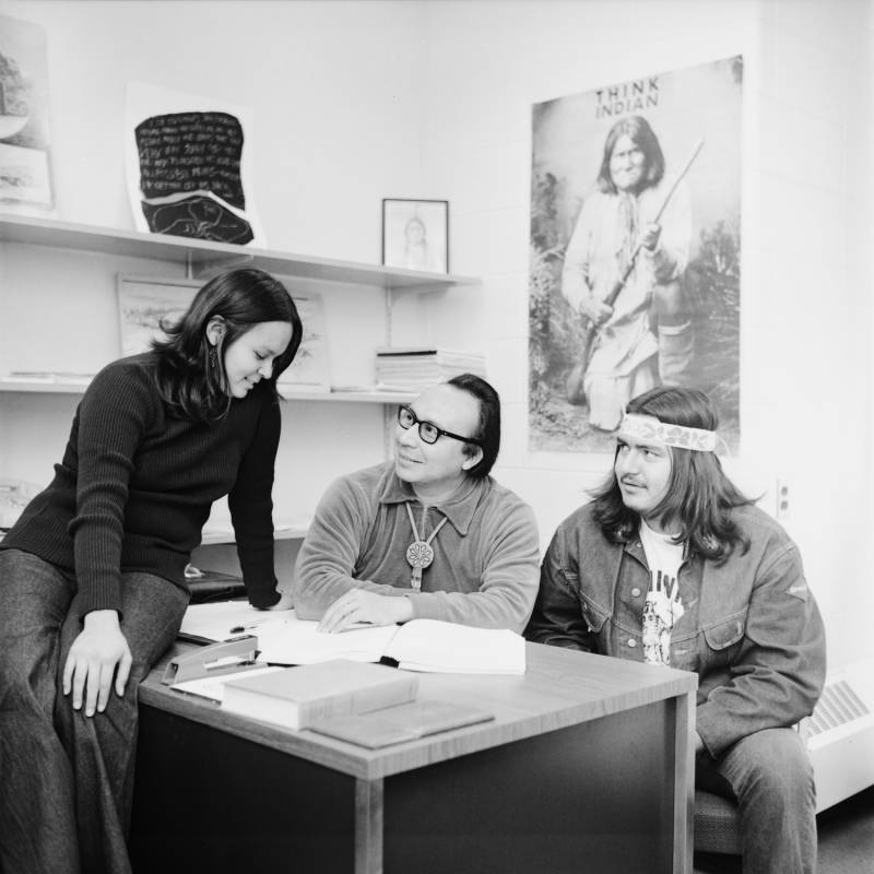 Robert Powless, UMD Indian Studies faculty and Ojibwe man, seated in a classroom with two students.