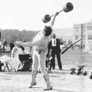 Athlete, weight lifting, standing on athletic field