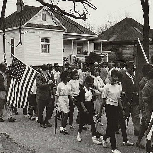 Participants, some carrying American flags, marching in the civil rights march