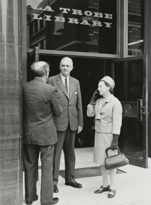 Photograph of Justice and Mrs Starke, and another man, standing at the entrance to the La Trobe Library, State Library of Victoria