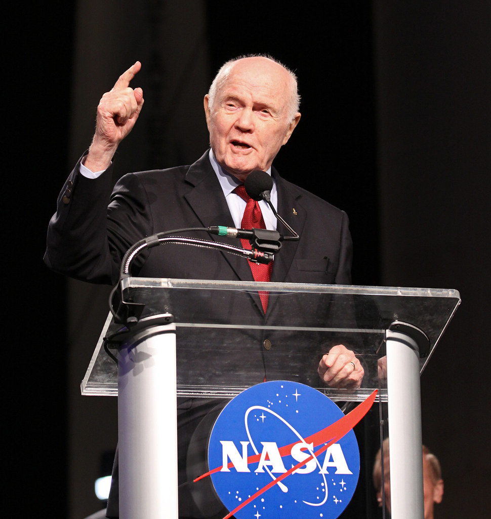 John Glenn at podium with NASA logo