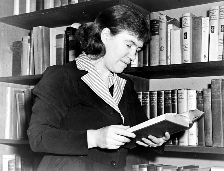 Margaret Mead holding a book in front of bookcase