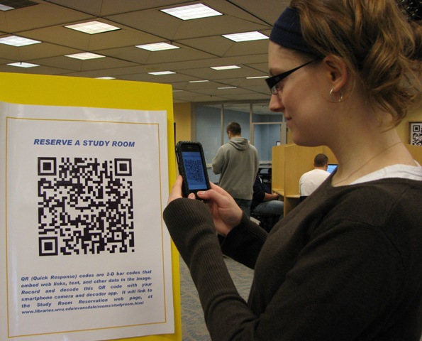 student in the library scanning a qr code that will explain how to reserve a study room