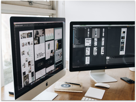 Two monitors displaying a website