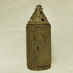 Metal lantern with holes and slits punched out.