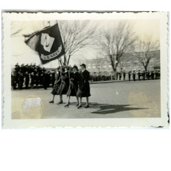 Photo of women in uniform marching, carrying a US Navy flag