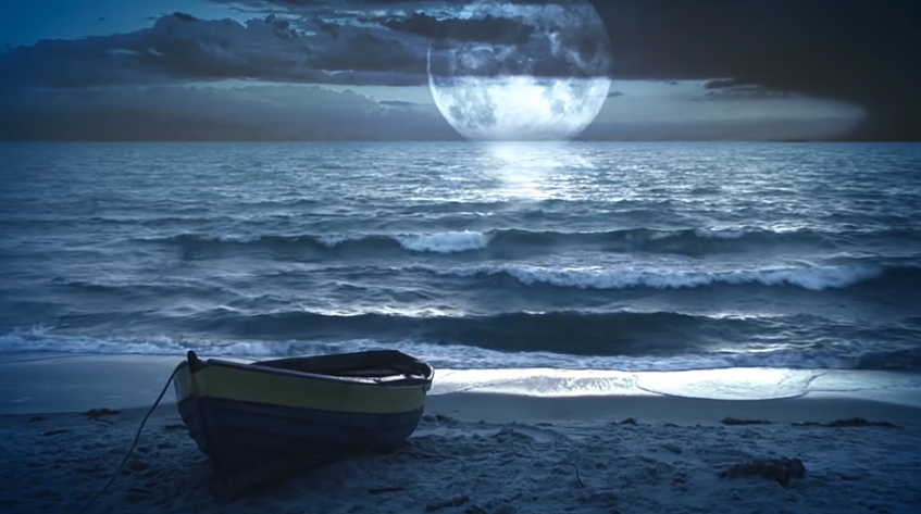 Ocean at night with a boat at the beach under a full moon