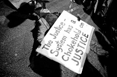 "demonstrator lying in street, holding a large sign that says ""The Justice System has a Chokehold on JUSTICE."""