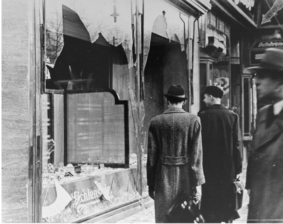 Photo: Germans pass by the broken shop window of a Jewish-owned business that was destroyed during Kristallnacht.