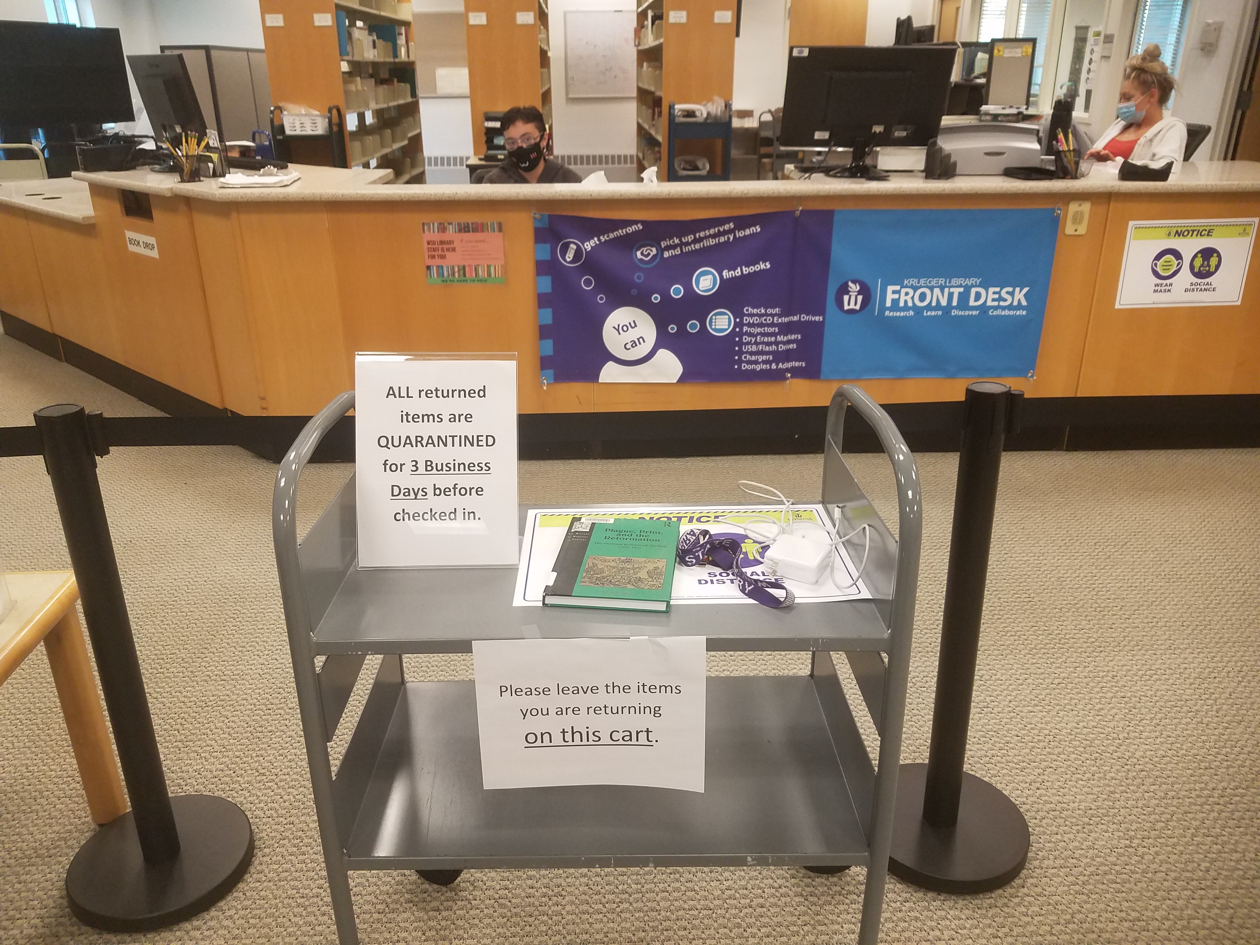 picture of book cart with signs about quarantining returned items