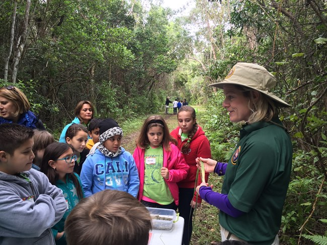 female volunteer working with children in a conservation area