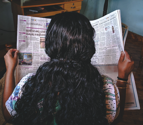 back of woman holding newspaper