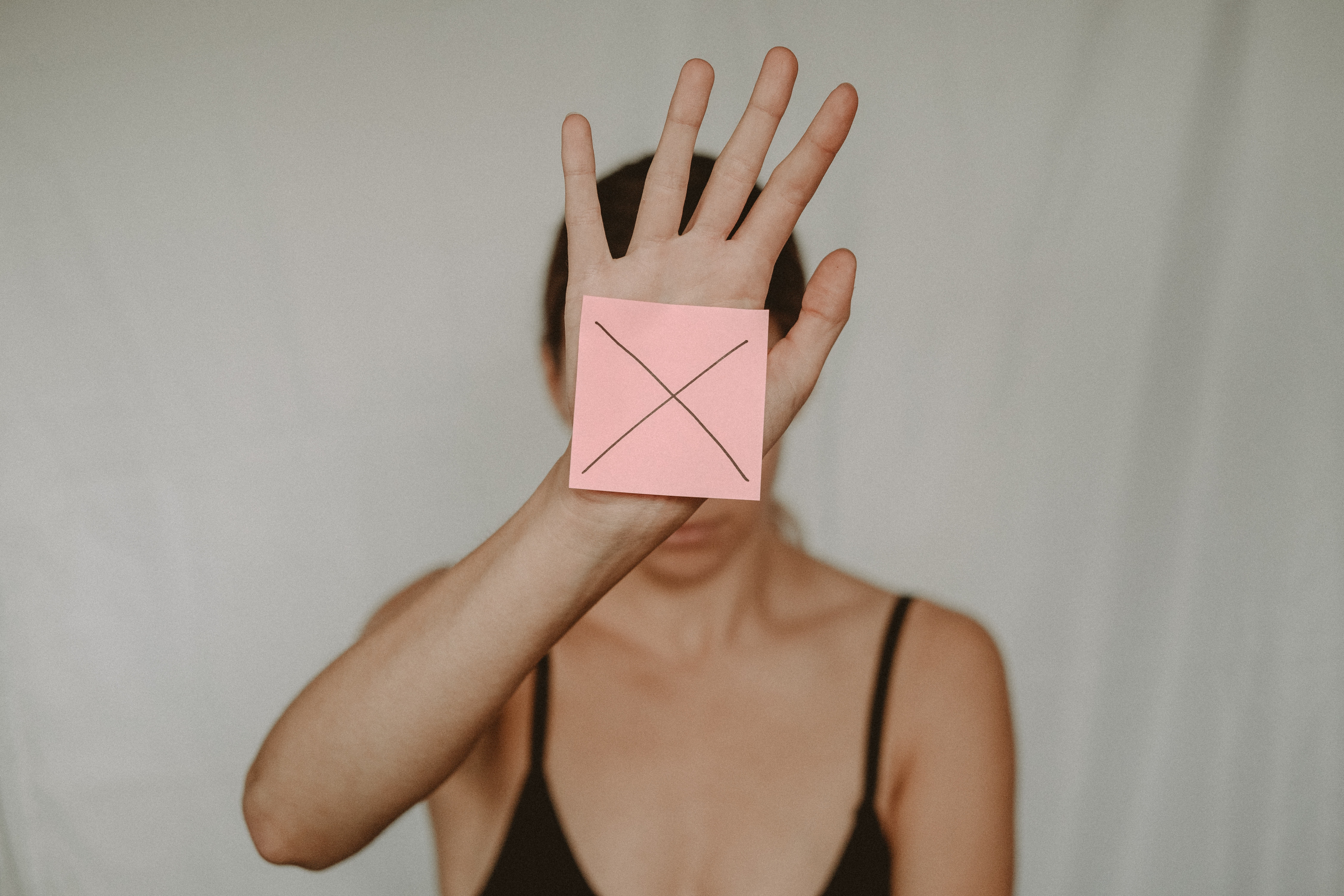 Woman holding out arm with note that has an X