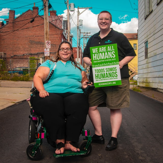 image of two individuals, one in a wheelchair, facing the camera with a disability rights poster