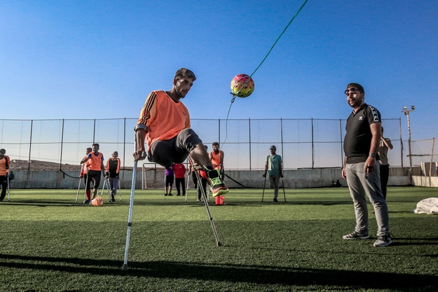 men playing soccer on grass field, one man has assisted technology for his leg