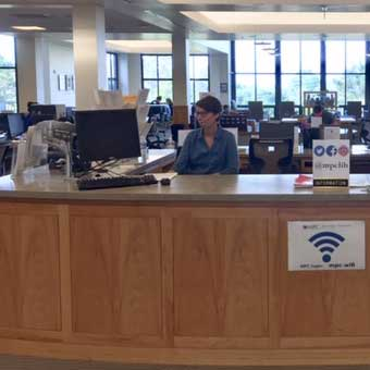 Photo of a librarian at the reference desk working on the computer.