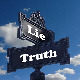 Photo of a cross street sign. One says Lie, the other says truth