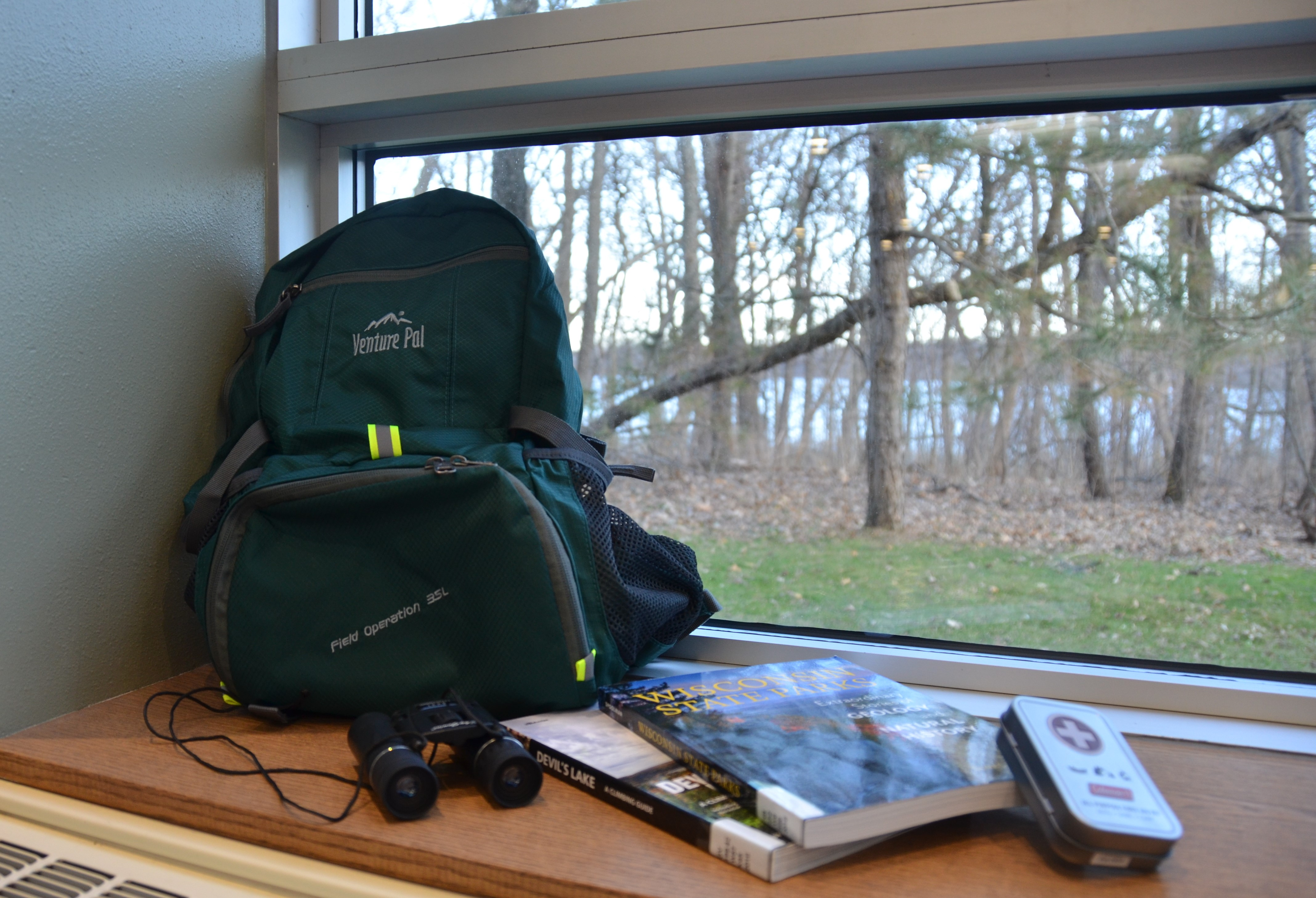 Photo of Devil's Lake State Park Backpack which contains two books about Devil's Lake, binoculars, and a first aid kit.