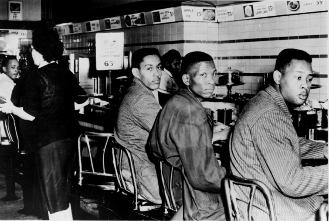 Original caption - Greensboro, N.C. : A group of Negro students from North Carolina A&T College, who were refused service at a luncheon counter reserved for white customers, staged a sit-down strike at the F.W. Wollworth store in Greenboro 2/2. Ronald Martin, Robert Patterson and Mark Martin are shown as they stayed seated throughout the day. The white woman at left came to the counter for lunch be decided not to sit down. UPI TELEPHOTO