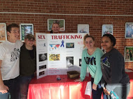 Five people gathered around their Change Your World Week display about sex trafficking