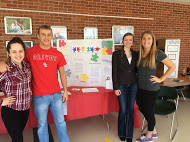 Four people gathered around their change your world week display