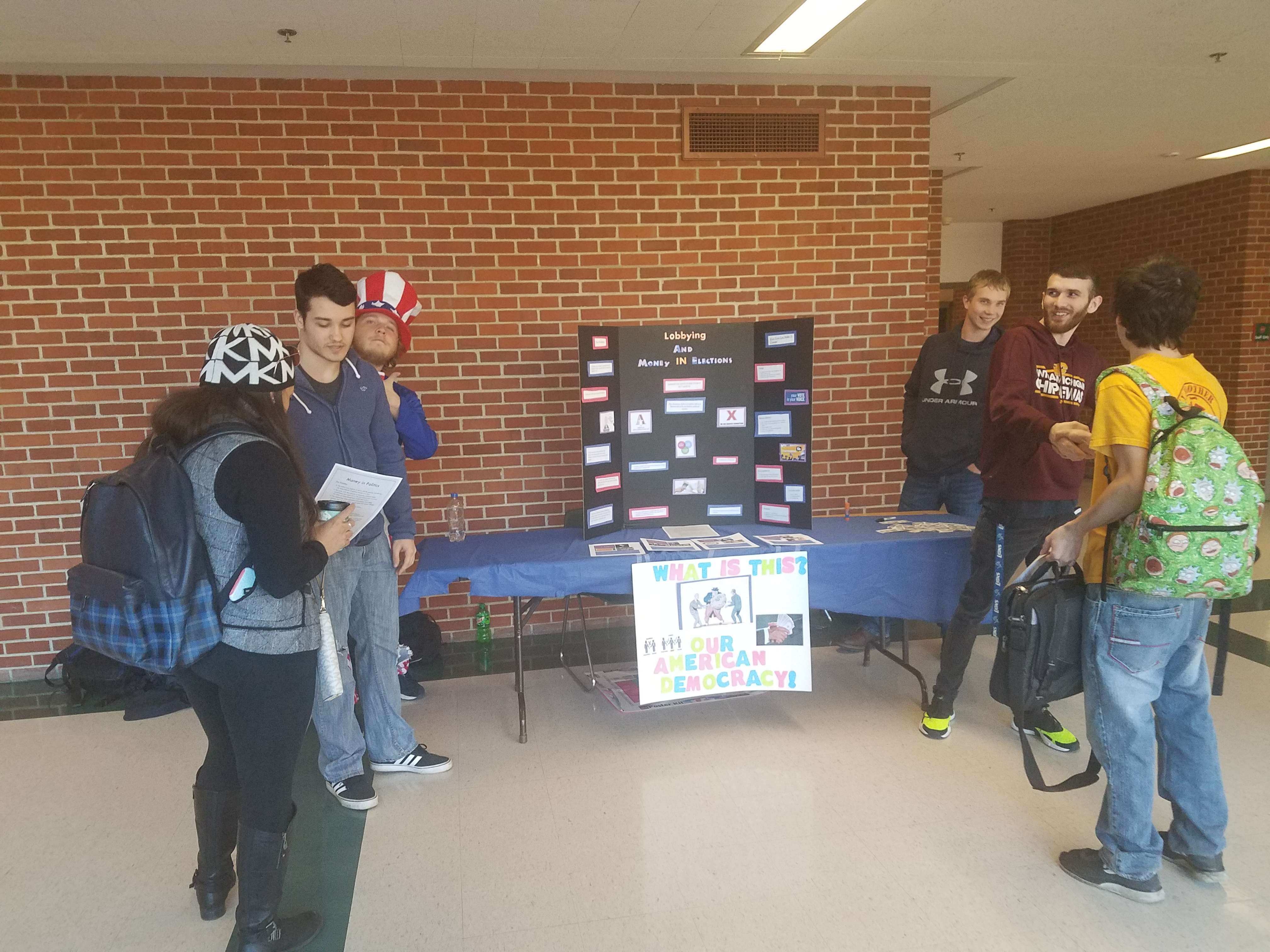 Six people around a change your world week display. One person is dressed as Uncle Sam.