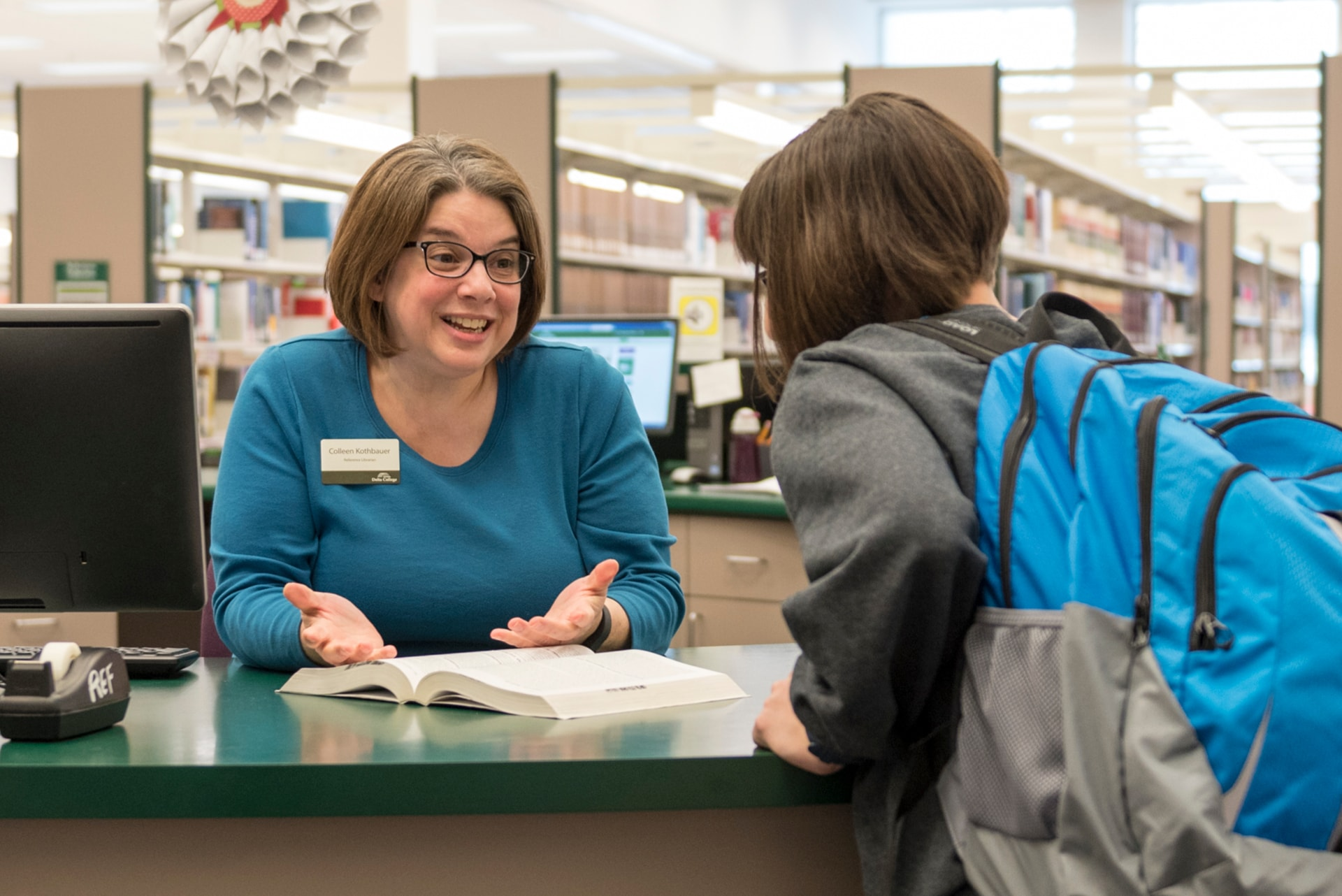 A student asks a smiling librarian for help at the reference desk