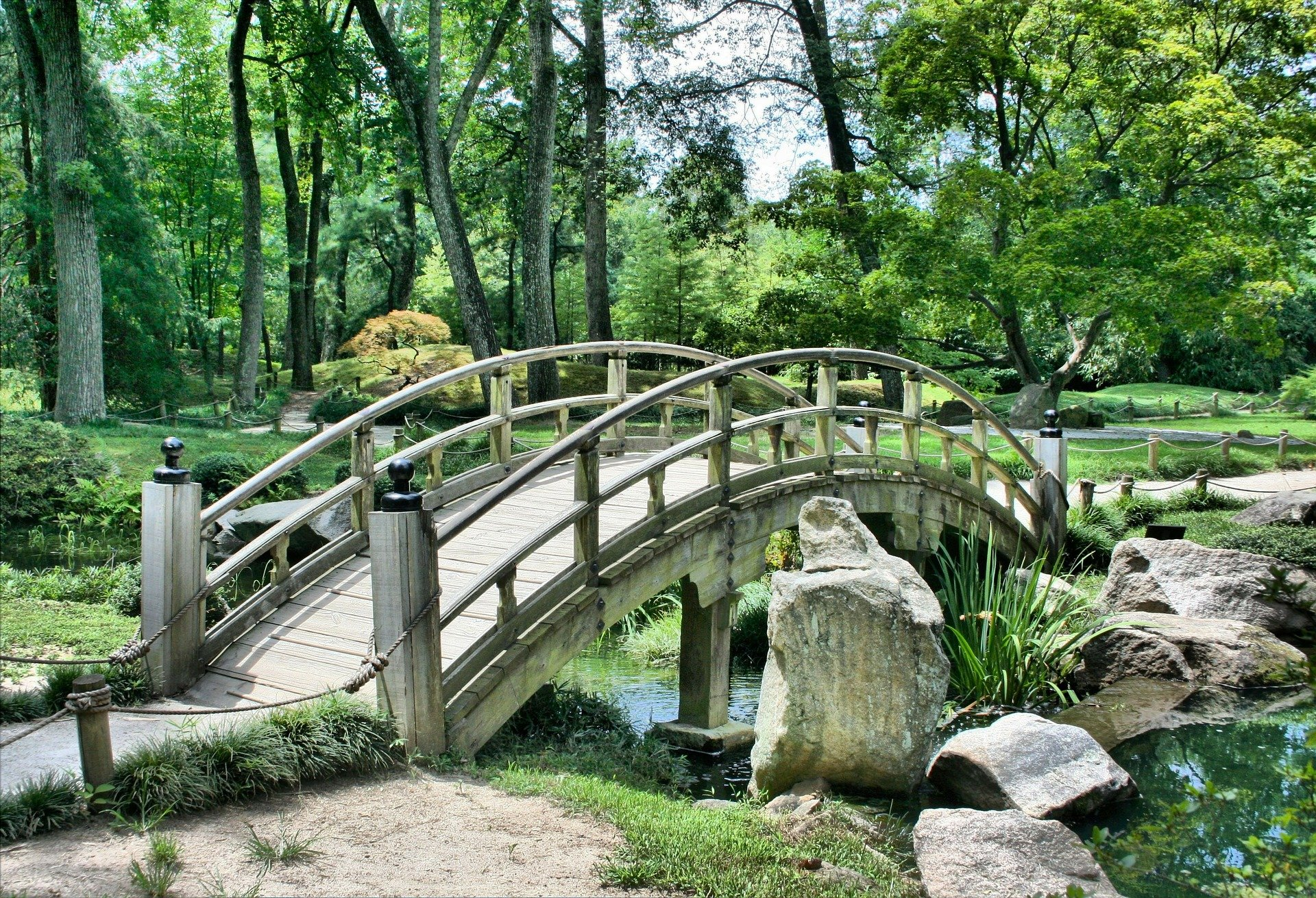 photo of garden with arched wooden bridge over stream