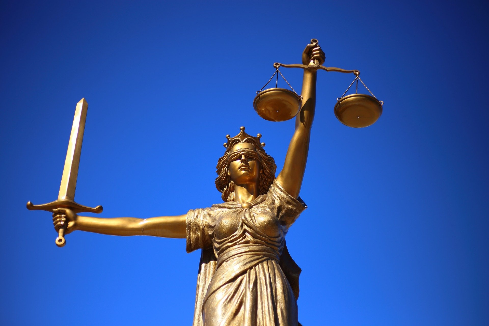photo of gold statue of lady justice holding scales and sword