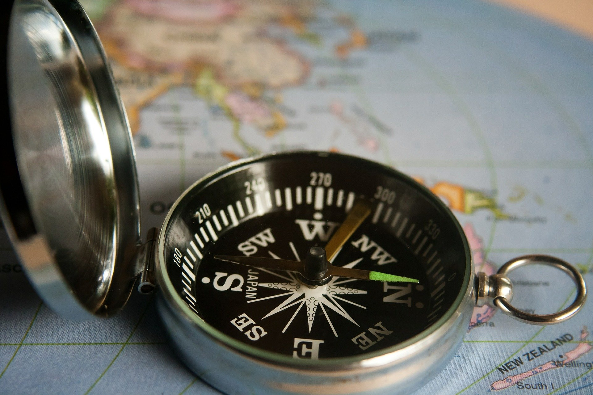photo of open compass sitting on top of map