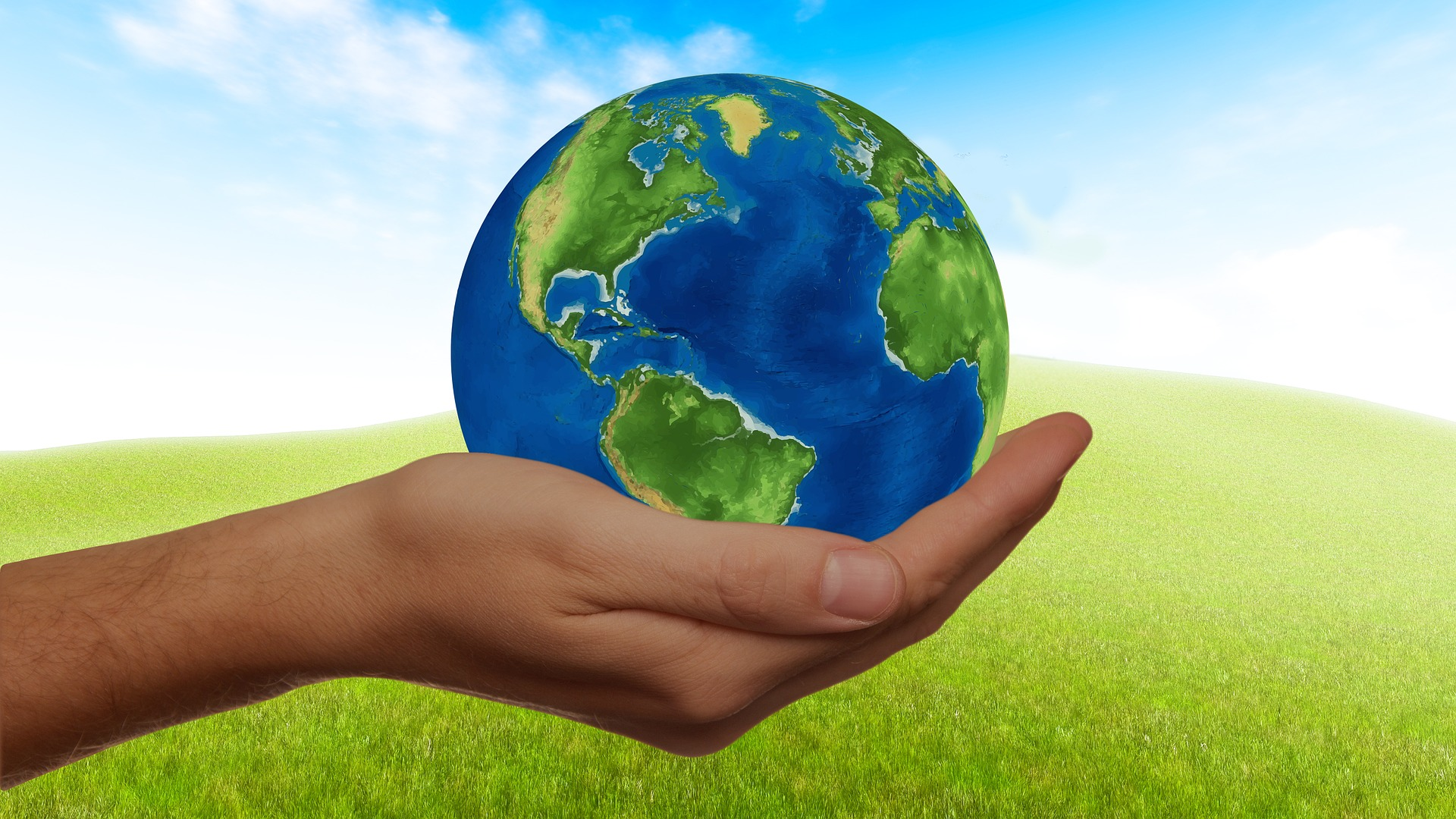 hand holding earth against blue sky background