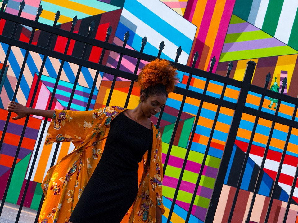 African American girl standing in front of colorful striped wall art and black fence