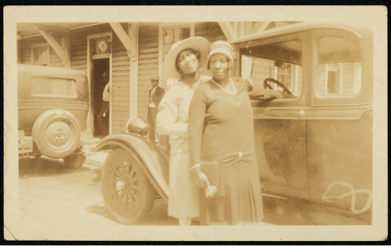Two African American women standing in front of a car during the 1920s or 1930s