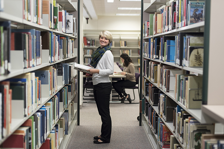 Woman standing in the rows between book shelves at the Delta College library