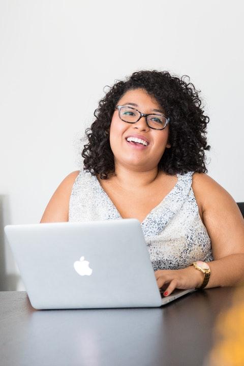 Smiling Hispanic woman at computer