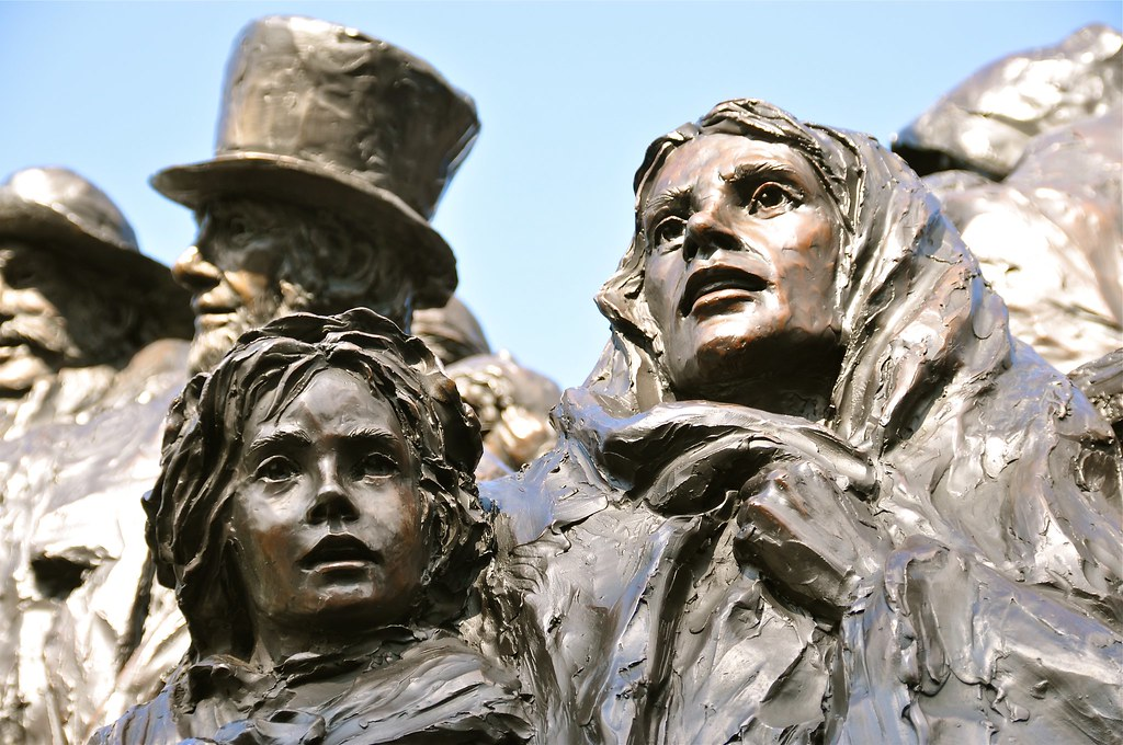 Part of the Irish Immigrant Memorial Statue focusing on a woman and a child. A man with a topcoat is in the background.