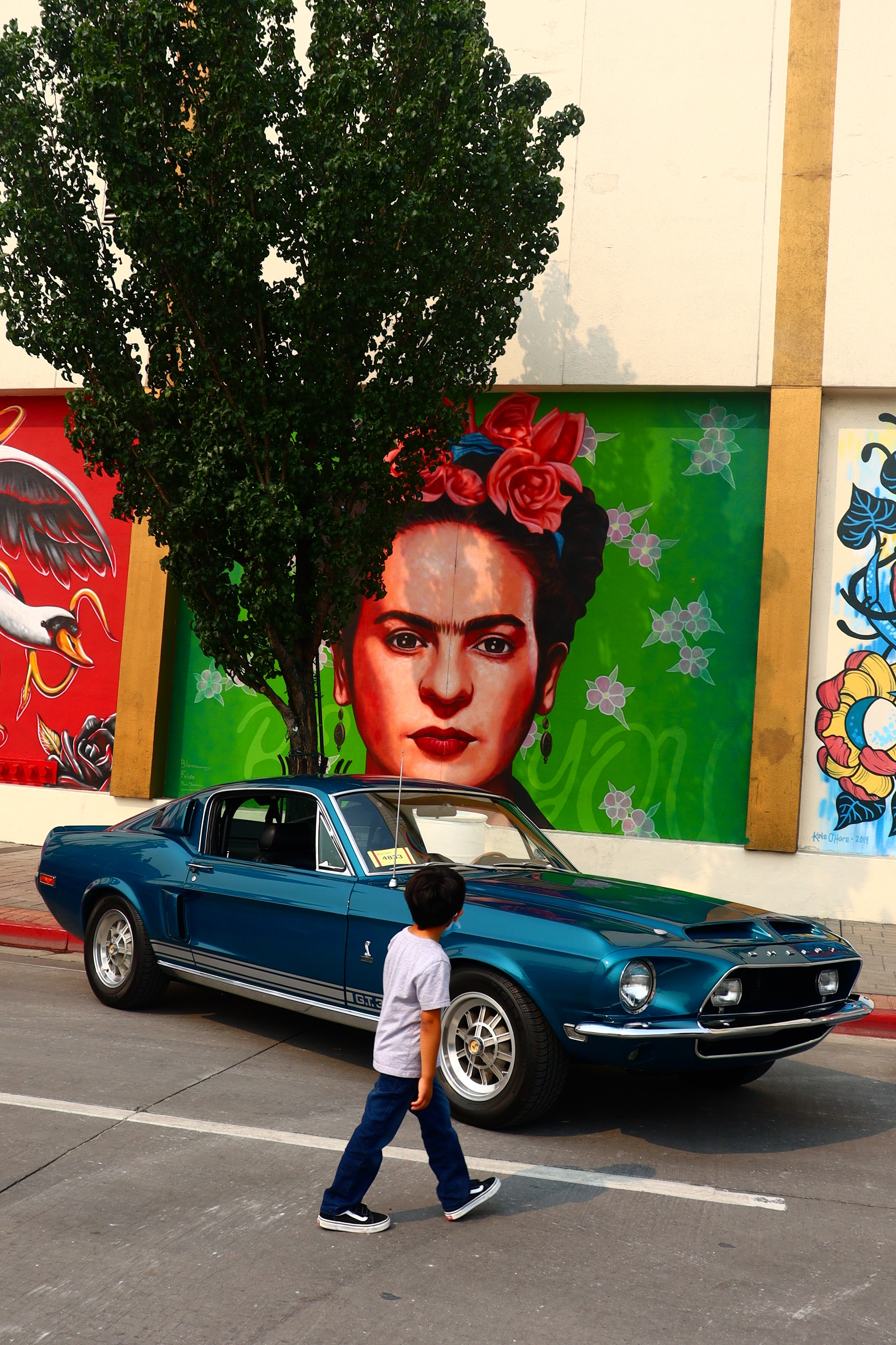 Young boy walking past a car parked in front of a mural of Fria Kahlo
