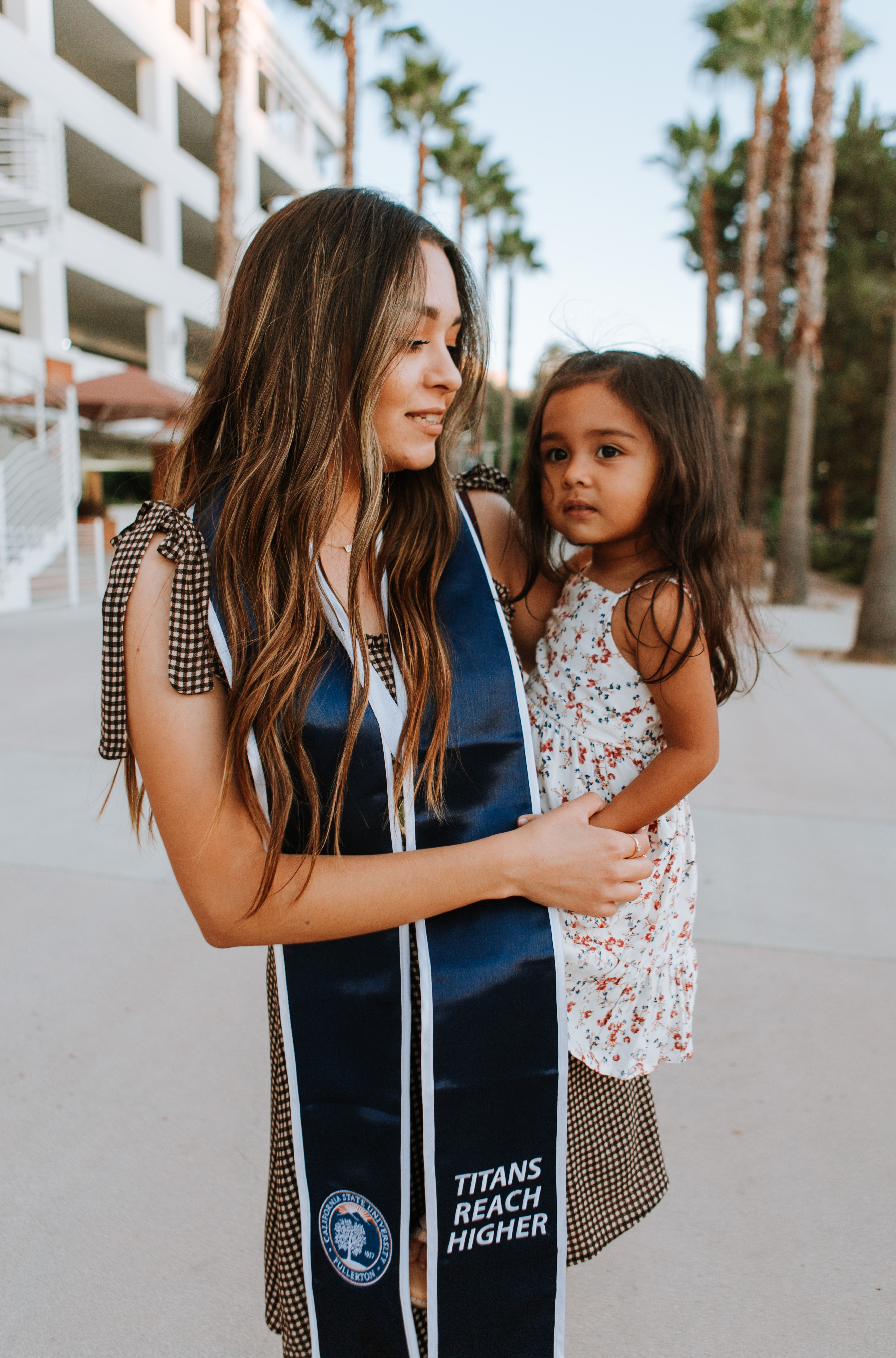 Latina woman graduate holding a toddler child on her hip